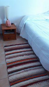 Jarapa, alfombra en tonos grises granate y naranja le da mucha calidez a tu dormitorio